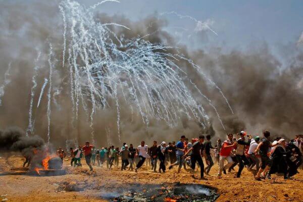 Los palestinos huyen del gas lacrimógeno durante los enfrentamientos con las fuerzas de seguridad israelíes. Fotografía: Mohammed Abed / AFP / Getty Images