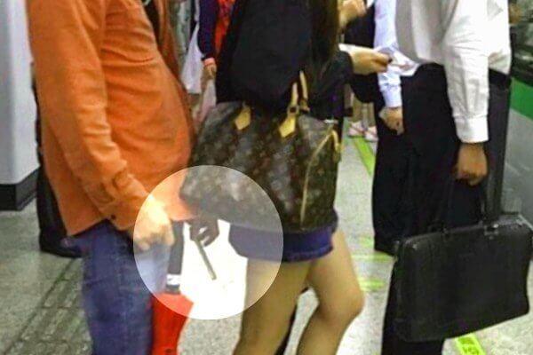 Un hombre tomando una foto bajo la falda de una mujer . Fotografía: East Asia Tribune