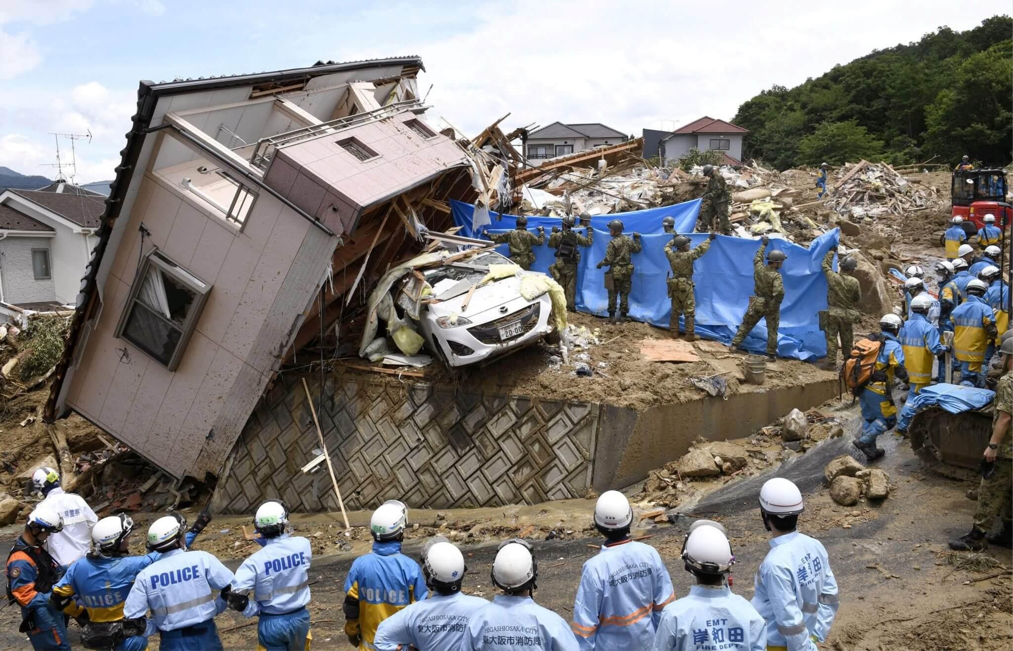 Rescatistas buscan personas desaparecidas en una casa dañada por fuertes lluvias en Kumano, prefectura de Hiroshima, el 9 de julio. Fotografía: Kyodo/Reuters