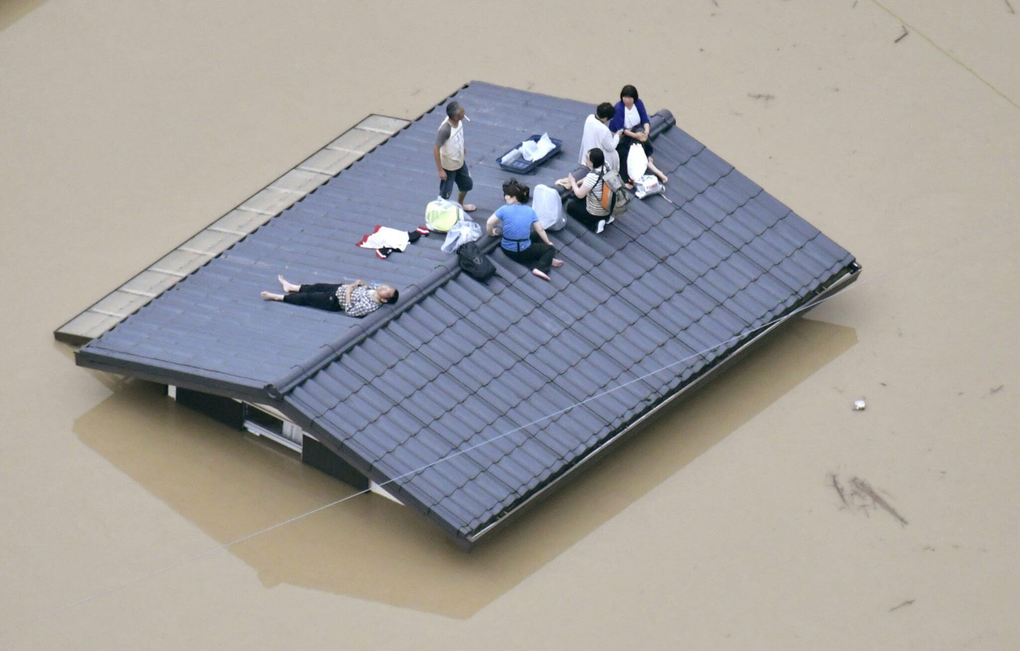 Una vista aérea muestra a los residentes locales vistos en el techo de una casa sumergida. Fotografía: Kyodo/Reuters