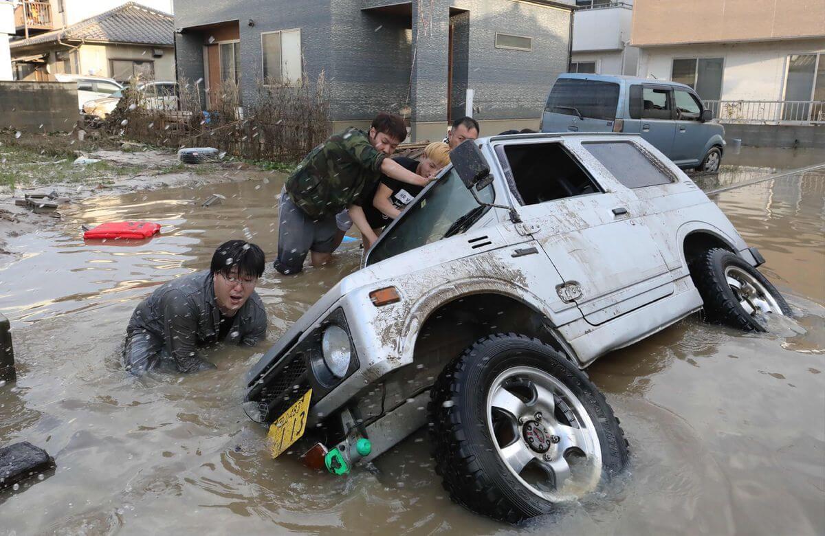 Los residentes intentan enderezar un vehículo atascado en una zona afectada por inundaciones en Kurashiki, prefectura de Okayama. Fotografía: AFP/Getty Images