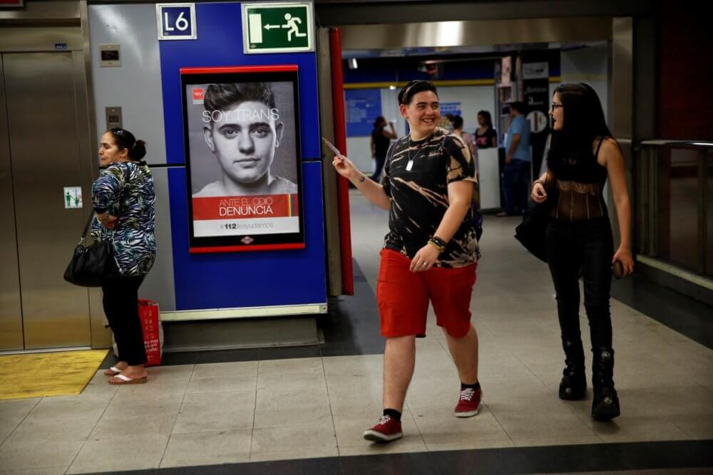 Gabriel apunta a uno de los afiches de la campaña que protagoniza por los derechos trans en el Metro de Madrid. Imagen: Susana Vera/Reuters