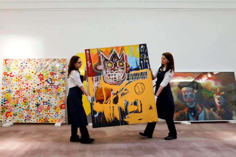 """Empleados de Sotheby's posan con """"Orange Sports Figure"""" de Jean-Michel Basquiat. Fotografía: JUSTIN TALLIS / AFP / Getty Images"""