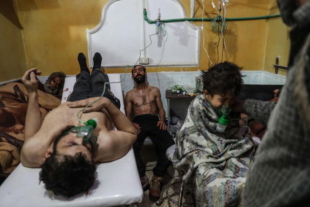 """Mohammed Badra, """"Las víctimas de un presunto ataque con gas reciben tratamiento en Ghouta del Este"""" (2018): Un hombre y un niño reciben tratamiento después del presunto ataque con gas en Al-Shifunieh, 25 de febrero de 2018. Imagen: © Mohammed Badra, European Pressphoto Agency"""