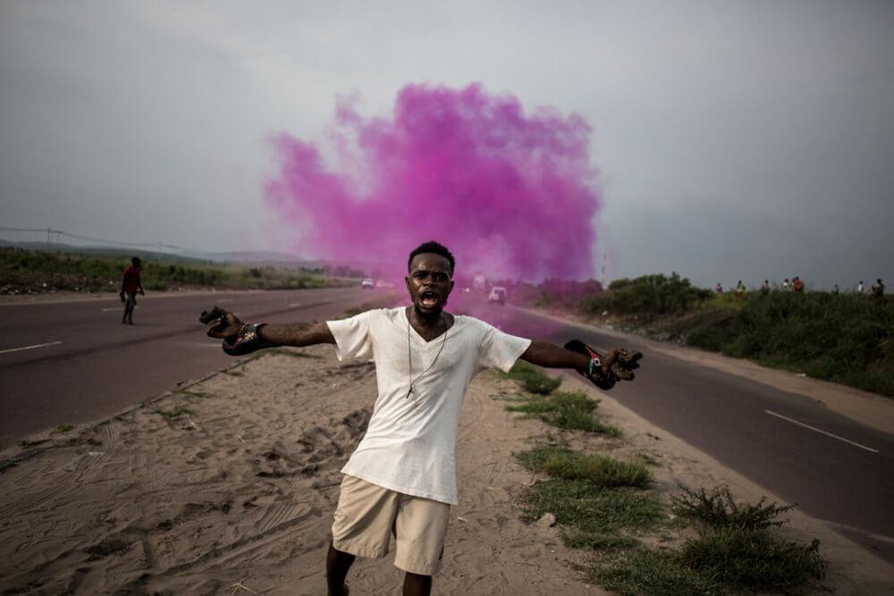 """John Wessels, """"Una lucha por la democracia"""" (2018): Un partidario de Martin Fayulu, líder de un partido de la oposición, huye de la policía de gas lacrimógeno en Kinshasa, el 19 de diciembre de 2018. Imagen: © John Wessels, Agence France-Presse"""