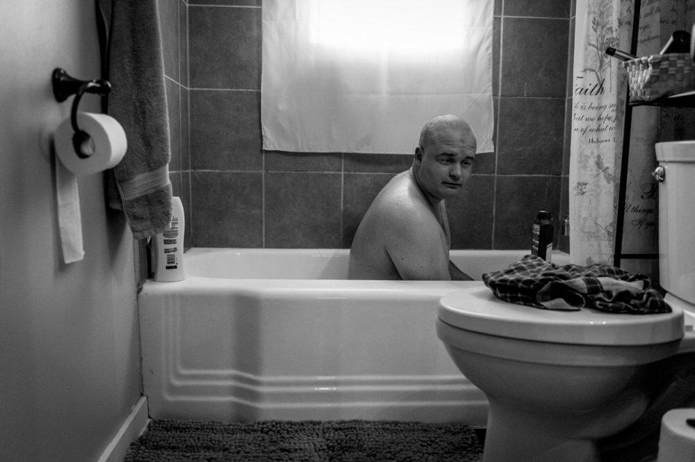 """Mary F. Calvert, """"Violación masculina"""" (2018): El ex marine de EE. UU. Ethan Hanson se baña en su casa en Austin, Minnesota, EE. UU., después de que un trauma sexual experimentado durante su servicio militar lo dejó incapaz de bañarse en una ducha. Imagen: © Mary F. Calvert"""