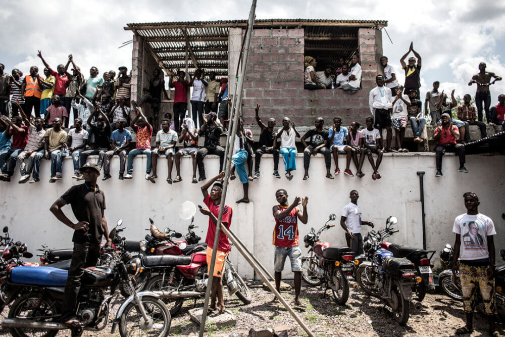 """John Wessels, """"Una lucha por la democracia"""" (2018): Simpatizantes de UDPS se reúnen fuera de la sede del partido, el 21 de diciembre de 2018. Un incendio que destruyó el equipo de votación llevó a otro aplazamiento de la elección, inicialmente previsto para el 23 de diciembre. Imagen: © John Wessels, Agencia France-Presse"""