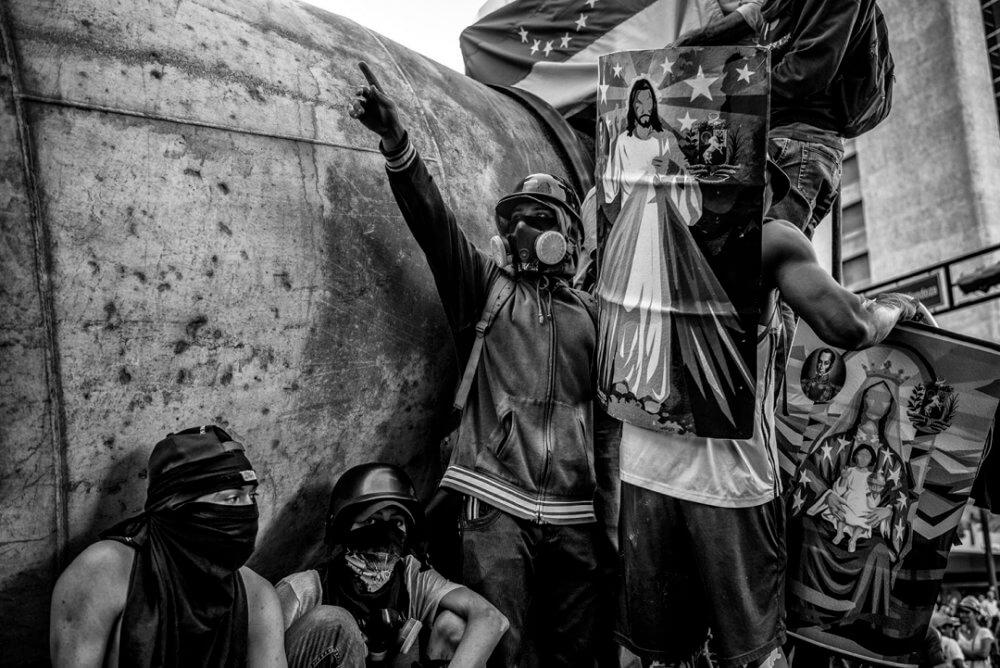 """Alejandro Cegarra, """"Estado de decadencia"""" (2017): Manifestantes con escudos caseros en una protesta contra Maduro, en Caracas, 7 de julio de 2017. Imagen: © Alejandro Cegarra"""