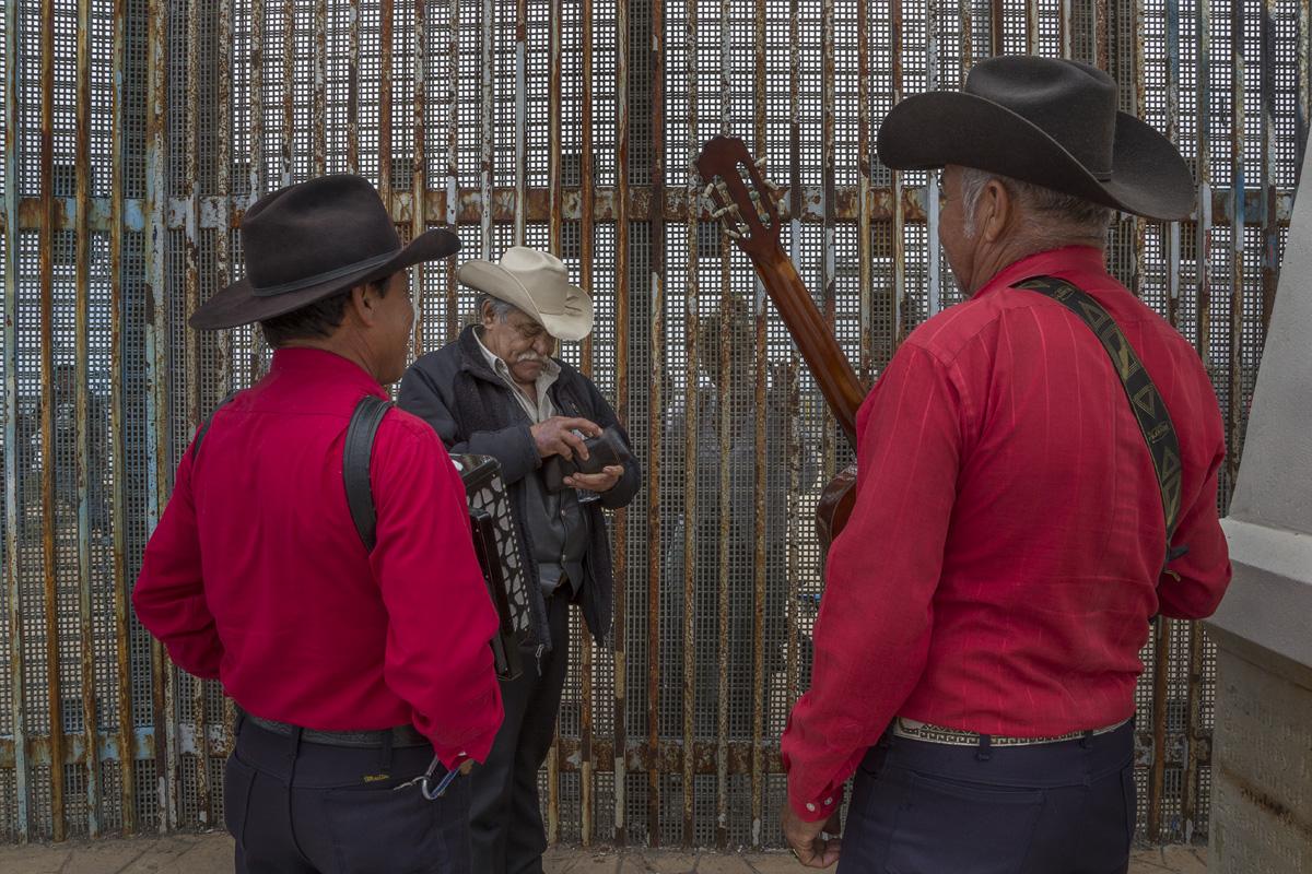 José Márquez contrata músicos norteños para cantarle una canción a su hija Susana, de 33 años, y a su nieto Johnny, de 14, que viven en San Diego y se acercan cada mes al muro fronterizo para poder pasar un rato en familia. Fotografía: Griselda San Martín